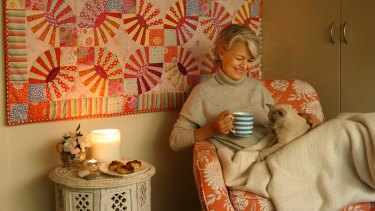 Danish-Australian Charlotte Thaarup is a proponent of the Danish concept of Hygge. Here she demonstrates the concept with a comfortable chair, blanket, candles, Danish pastries, tea, a book, and her cat Millie.