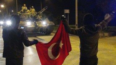Cheering Turks wave toward tanks heading toward the Syrian border, in Hatay, Turkey.