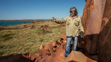 The rock art on the Burrup represent more than 30,000 years of continuous living culture. Senior cultural ranger at Murujuga National Park, Jakari Togo, looks out to sea next to rock carvings on the Burrup Peninsula.
