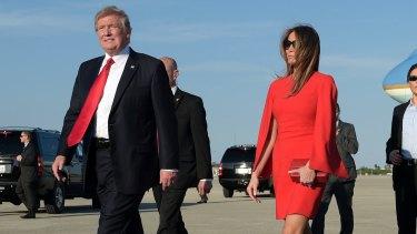 President Donald Trump walks with first lady Melania Trump.
