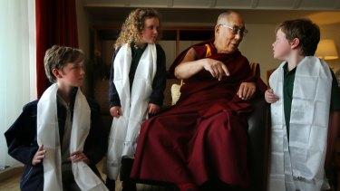 His Holiness the Dalai Lama  talks with Leura public school students Harry Skeggs 11 (left), Eliza Skeggs, 6, and Joe Skeggs, 9.
