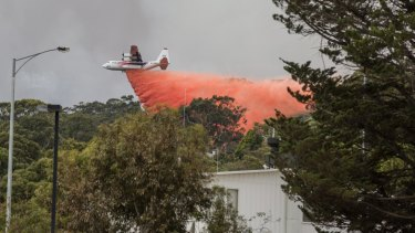 A waterbomber sprays fire retardant on bushland on the outskirts of Lorne on Christmas Day.