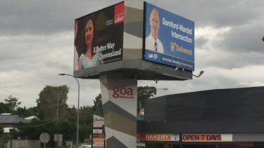 Annastacia Palaszczuk and Campbell Newman hold competing signs at the Samford Road-Wardell Street intersection in the seat of Ashgrove.