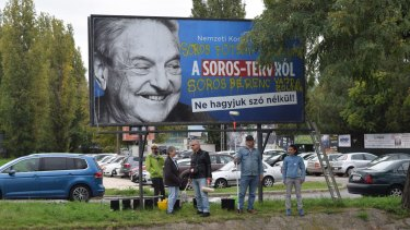 Activists stand in front of an anti-George Soros billboard. Soros said oppression of the opposition by Orban's government is greater than when Hungary was under Soviet domination.