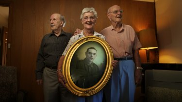 Keith Huntsman, Jean Oldfield and Clive Huntsman hold a photograph of their uncle Henry Huntsman.