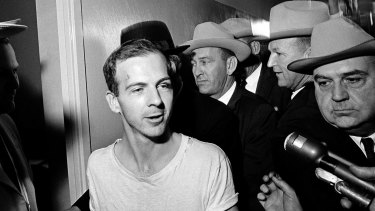 Lee Harvey Oswald talks to the media as he is led down a corridor of the Dallas police station in 1963.