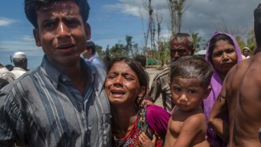 Rohingya Muslims, who crossed over from Myanmar into Bangladesh, mourn for a family member who drowned when the boat they were traveling in capsized minutes before reaching the shore, at Shah Porir Dwip, Bangladesh.