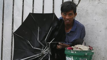 A boy holding a broken umbrella seeks shelter from the winds and rain in Manila.