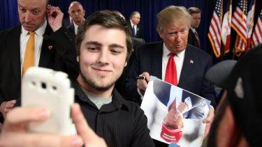 Nathan Lanferman, 17, of Newton, attempts to take a picture of Republican presidential candidate Donald Trump following a rally at Des Moines Area Community College in Iowa.