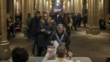 A woman casts her ballot for the Catalan regional elections at a polling station in Barcelona, Spain.