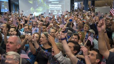 Guests and New Horizons team members count down to the spacecraft's closest approach to Pluto.