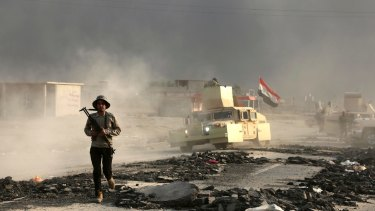 Iraqi soldiers are seen outside the city of Mosul on Wednesday, on the third day of the battle to retake the city from IS.