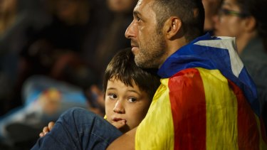 A man and his child listen to a televised speech by Spain's Prime Minister Mariano Rajoy after a banned Catalan referendum in Barcelona.
