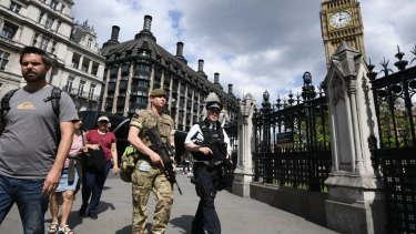 An armed soldier and an armed police officer patrol outside the Houses of Parliament.