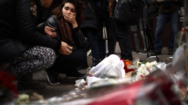 A woman reacts after places flowers near the  Bataclan Concert Hall.