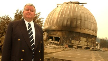 Then vice-chancellor of the ANU, Ian Chubb, stands beside the main 74inch telescope dome after the fires.