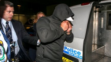 Ahmad being escorted into a police van by officers after he arrived at Sydney airport.