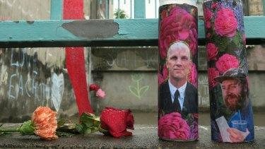 Votive candles bearing the photos of two men who were fatally stabbed in Portland, Oregon.