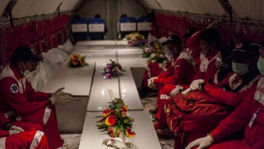 Members of Indonesian red cross watch over the ten coffins containing victims of the AirAsia flight QZ8501 crash.