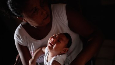 Alice Vitoria Gomes Bezerra, 3-months-old, who has microcephaly, is held by her mother.