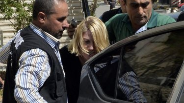 Lebanese policemen escort Tara Brown from a Lebanese courthouse before the deal was struck.