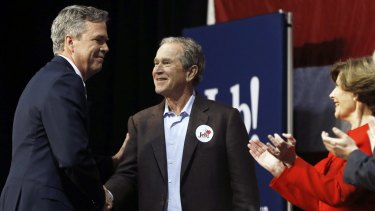 Republican presidential candidate and former Florida governor Jeb Bush, left, shakes hands with his brother, former president George W. Bush.
