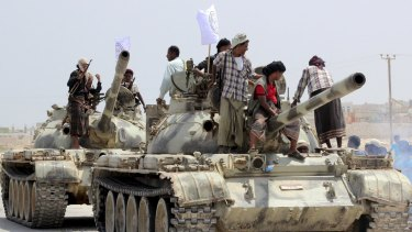 Tribesmen stand on tanks they took from army bases in Shihr city in Yemen's eastern Hadramawt province on Saturday.