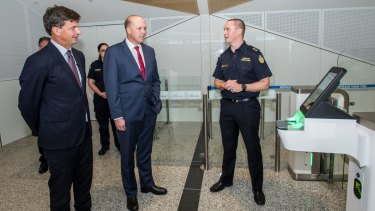 Ministers Angus Taylor and Peter Dutton check out one of the old SmartGates in the international departure lounge at Canberra Airport.