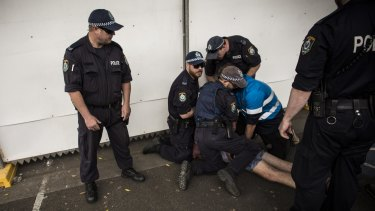 Police attend to a festivalgoer at Sydney Olympic Park.