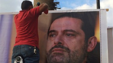 "Workers hang a poster of outgoing Prime Minister Saad Hariri with Arabic words that read, ""We are all Saad,"" on a seaside street in Beirut, Lebanon, on Thursday."