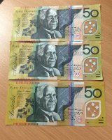 Spot the difference: The top two notes are fake, the bottom one is real.