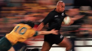 "Jonah Lomu evades the tackle of Stephen Larkham during the ""greatest game of all time"" in Sydney, 2000."