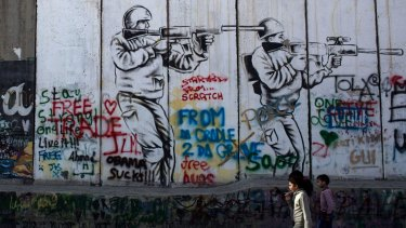 Children walk past graffiti painted on the Palestinian side of the separation wall in Bethlehem, in the Israeli-occupied West Bank.