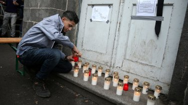 A young man lights a candle at a makeshift memorial to a young Syrian man believed to have died while waiting to receive government benefits.