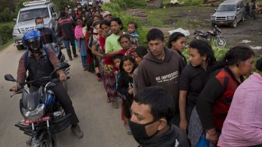 Nepalese villagers line up to receive food being distributed in Sakhu, on the outskirts of Kathmandu, on Wednesday.