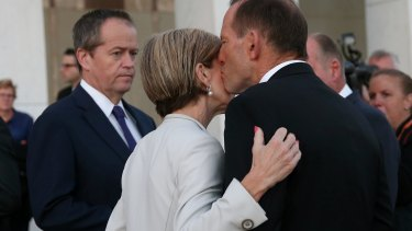 Unity: Bill Shorten looks on as Tony Abbott kisses Julie Bishop.