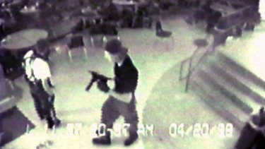 Eric Harris, left, and Dlyan Klebold, carrying a TEC-9 semi-automatic pistol, are pictured in the cafeteria at Columbine High School, in Littleton, Colorado, during their shooting rampage in 1999.