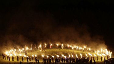"""Members of the Ku Klux Klan participate in cross burnings after a """"White Pride"""" rally in April."""