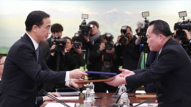 Representatives from North and South Korea exchange a joint press release after the first inter-Korean high-level talks in over two years on January 9.