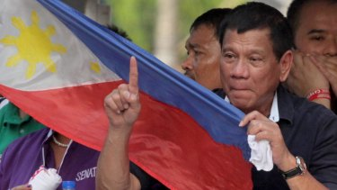 Presidential candidate Mayor Rodrigo Duterte holds a Philippines flag as his campaign motorcade makes its way through the streets of Malabon, Philippines.