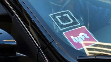 A driver displaying Lyft and Uber stickers in the US.