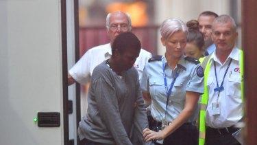 Akon Guode is taken into the Supreme Court on Wednesday.