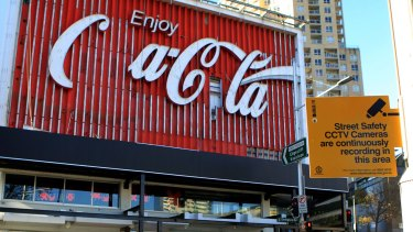 The iconic Coca-Cola sign, undergoing an update, stands amid the watchful eye of CCTV.
