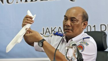 Soerjanto Tjahjono holds a model plane during the news conference.