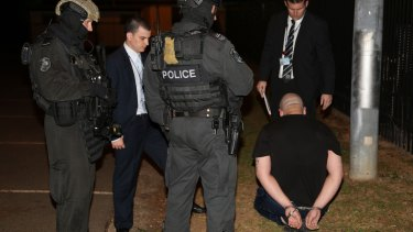 A man is arrested during the drug raids in Sydney.