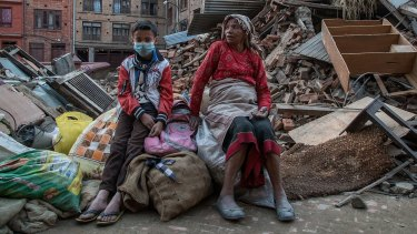 A grandmother and her grandson sit on the belongings that they have salvaged from their collapsed home in Bhaktapur on Wednesday.