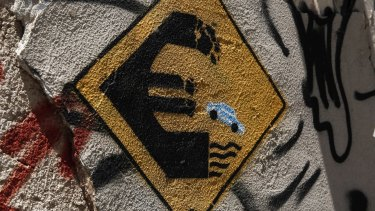Graffiti depicting a car driving off a euro sign into water on a wall of an abandoned house in Athens.