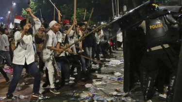 Protesters use sticks to attack riot police.