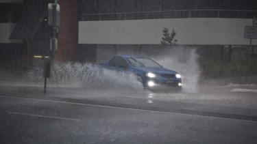 A car drives through water over the road after heavy rain.