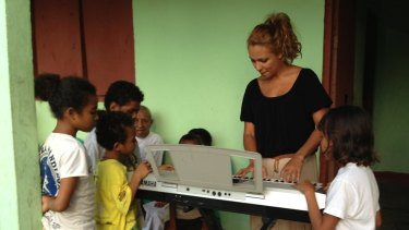 Ambre Hammond plays for children in Dili.